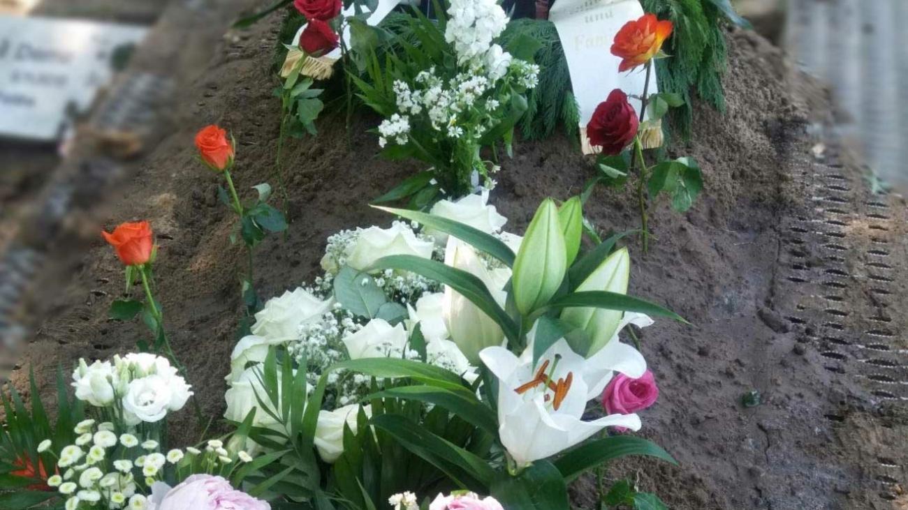 Arslans Grab mit vielen Blumen und einem Foto von ihm
